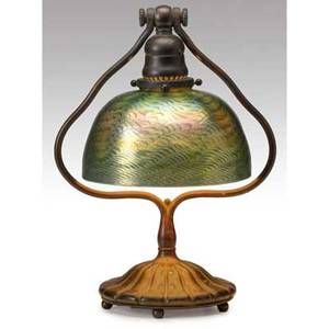 Tiffany studios table lamp with rotating harp and fluted base and faceted favrile glass shade in a pulledfeather motif fine original patina and socket a few scratches to base base stamped tiffan