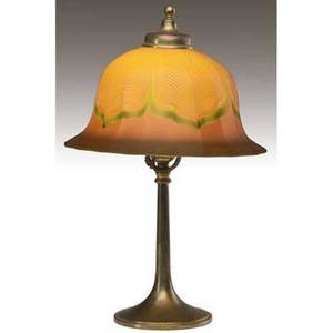 Tiffany  co  quezal table lamp with quezal art glass shade in white and green pulled feather motif on a gold ground over a singlesocket brass base shade etched quezal base stamped tiffany  co