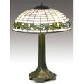 Bigelow kennard  co  weller table lamp with a leadedglass shade bordered in leaves over a weller mat green threesocket base in peacock feather pattern shade stamped bigelow  kennard studios bo