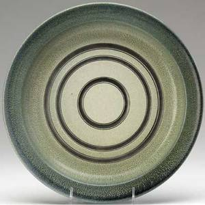 Glen lukens earthenware charger covered in green and indigo mottled glazes incised and painted with concentric silver circles 1 12 x 12