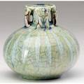 Adelaide robineau fine and rare porcelain vase the spherical base topped by four handles carved with irises covered in celadon and oxblood glaze the base with ribs of opaque celadon on crackled gro