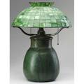 T j wheatley table lamp the bulbous threesocket base fitted with converted oil font and covered in matte green glaze with a period arts  crafts green leaded slag glass shade shown in an interi