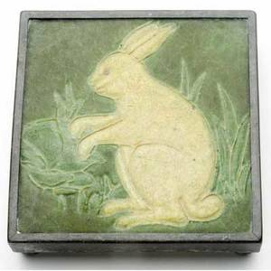 Grueby rare tile decorated in cuenca with a crouching ivory rabbit in a lettuce field in dark green on lighter green ground set in original metal mount signed ca 6 sq