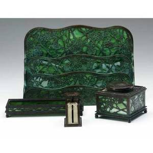 Tiffany studios four desk set items in the grapevine pattern backed in green slag glass pen tray inkwell scale and large letter holder exhibited in amercan arts  crafts from the collection of