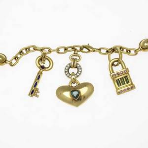 Gemset gold charm necklace 18k yg oval link chain with two kinetic bead stations suspends heart with inset tourmaline from a diamond pave disk ca 1985 gemset lock and key charms set with tourmali