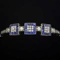 Early art deco diamond  sapphire bracelet silvertopped yg ca 1911 the central fixed arch designed with channels of sapphires around oec diamond clusters and boxset diamonds tapers to diamond an