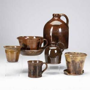 Seven pieces of redware pottery 19th c splotchdecorated jug and milk pitcher three manganesedecorated pieces and two flower pots some with damage tallest 9