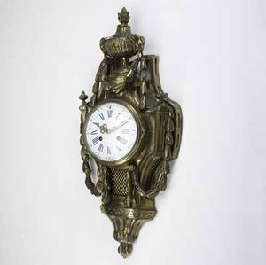 French cartel clock 19th c in brass case with porcelain dial eight day time and strike movement urn finial with rams head mountings and swag decoration 27
