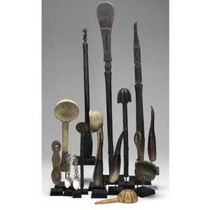 Collection of fifteen african cooking and eating utensils seven spoons four ladles three spatulas and one churn showing wear consistent with field use each on a custom base consisting of three e