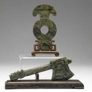 Two jade carvings 20th c one spinach color with an axe with serpent handle on wood stand the other a small elongated disc on stand larger 12 x 5
