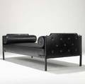 Jacques adnet daybed covered in stitched black leather with brass hardware and two bolster cushions 27 x 28 x 75