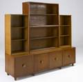 Morris sanders  mengel sevenpiece modular stacking cabinet with four open shelving units resting on three cabinets two singledoor and one doubledoor all with circular wood and brass pulls ca 1