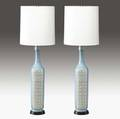 Guido gambone pair of tall ceramic table lamps with panels of alternating geometric forms in green on a white and blue ground with cylindrical linen shades one marked with partial paper label potte