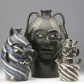 Charles lisk three folk art face jugs one of marbleized clay with several openings and blue eyes 10 one of swirled brown white and blue clay 13 and a large one with blue eyes and dripping glaze
