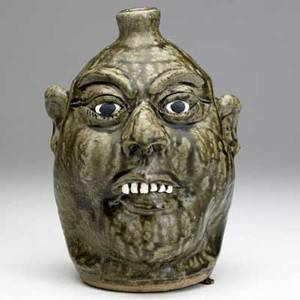 Lanier meaders face jug with smiling expression and clay teeth covered in alkaline glaze signed lanier meaders 9 12