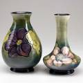Moorcroft two vases in the anemone pattern on celadon or dark green both stamped moorcroft made in england potter to the queen and green ink signatures one with paper label 8 12 and 8 14