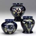 Moorcroft three cabinet vases one in the pansy pattern one orchid and one freesia all stamped moorcroft made in england two with paper label tallest 3 12