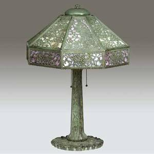 Bradley  hubbard attr table lamp with a pierced and faceted shade of peacocks and vines lined in slag glass over an oak leaf twosocket bronze base with verdigris patina unmarked 24 x 16 12
