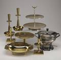 Tommi parzinger  dorlyn silversmiths  mueckcary eight assorted metal pieces seven by dorlyn silversmiths two pairs of candlesticks a covered casserole dish with glass insert and a tazza all in