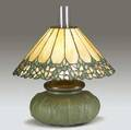 hampshire  unique table lamp with hampshire squat base embossed with tulips and covered in matte green glaze topped with its original converted oil font glass chimney and unique leaded glass sh