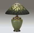 grueby  handel table lamp with a grueby base decorated with tooled and applied fullheight leaves alternating with yellow buds against a rich matte green ground the base is fitted in a handel elec