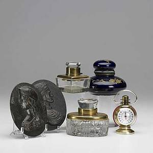 Desk accessories six pieces two bronze plaques with classical figures two lidded crystal inkwells with brass mounts porcelain inkwell with cobalt glaze and gold leaf design and art deco french the