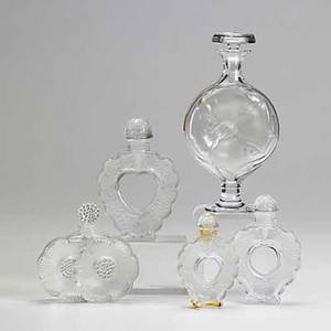 Lalique five perfume bottles include three figural hearts in descending size dogwood and double daisies 20th c all marked tallest 6 34