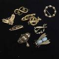Brooches nine pieces 19th20th c victorian mourning brooch with black enamel in 10k yg etruscan revival with branch passing through interlocking rings in 10k yg floriform pin with opal and garne