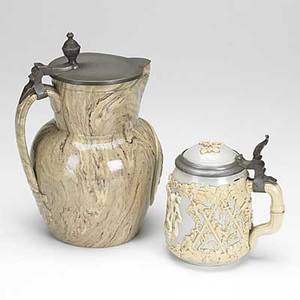 Mettlach attr covered beer stein with cartouche and applied decoration together with a similar covered pitcher stein 6 x 5 12 x 4 dia