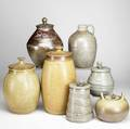Gary baxter seven pieces of stoneware include two similar covered jars three jars with stemshaped handles jug and covered urn decorated with a leaping hare in sgraffito each signed tallest 16 1