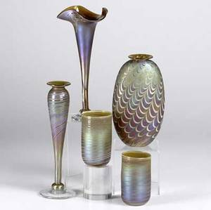 Craig zweifel five iridescent art glass pieces include baluster shaped bud vase flaring vase with ruffled rim bottle shaped vase and two tumblers all with pulled decoration each signed most dated