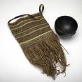 Tribal items phillippino carved wooden bowl with twine strap early 20th c kenya potato bag woven grass with fringe and strap handle mid20th c largest 22 x 7 12 dia