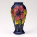 Moorcroft tall vase decorated in the hibiscus pattern over indigo glaze stamped moorcroft made in england 12 12