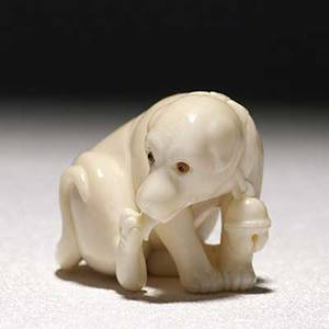 Japanese ivory netsuke depicting a dog with inlaid eyes licking his right hind paw 20th c signed ikku 1 38 x 1 34