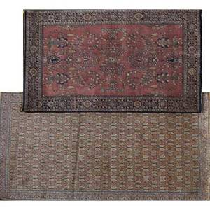 Two oriental area rugs one with red background and blue border the other with rose floral design 20th c larger 54 x 83