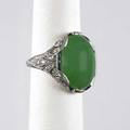 Art deco jadeite platinum diamond ring oval apple green jade cabochon 165 x 122 x 6mm approx 9 cts bordered by rows of small french cut sapphires in pierced diamond scroll setting 24 diamonds