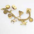 Charm bracelet nine charms most 18k pocketbook conceals gold dice chalet conceals sleepers in enameled bed horse dog hat california gold coins 1853 and 1856 etc 545 gs 7