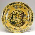 Dish with confronting dragons the interior decorated with an incised outline enclosing two fiveclawed dragons in pursuit of a flaming pearl amidst clouds the exterior with four further dragons a