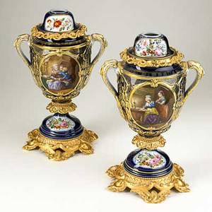 Pair of continental porcelain urns handpainted figural decoration with gilt bronze mounts 20th c unmarked 16 x 10