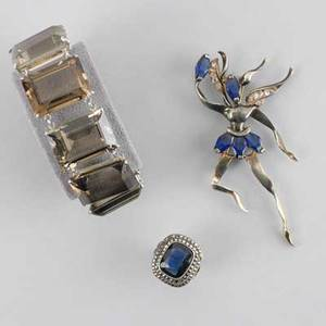 Three pieces sterling jewelry bracelet with smokey quartz marked mg 7 blue gem ring marked germany size 3 dancing fairy brooch with trapezoidshaped french cut blue gems 3 12 all marked