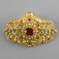 14k yellow gold gemstone brooch openwork in the rococo style with garnet aquamarines emeralds and rubies in cut collets and seed pearls 18k pin stem with french import mark replaced clasp 15