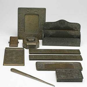 Tiffany studios ten assembled desk set pieces in the zodiac pattern new york 1920s blotter ends calendar paper clip letter opener pen tray cigarette box desktop frame inkwell and letter ho