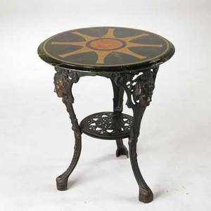 Wrought iron garden table base decorated with faces of women faux marble top 20th c 28 x 24 dia