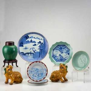 Asian porcelain and pottery nine pieces 20th c pair of foo dogs celadon plate celadon and blue and white scalloped edge bowl green monochrome ginger jar etc some marked tallest 9 12