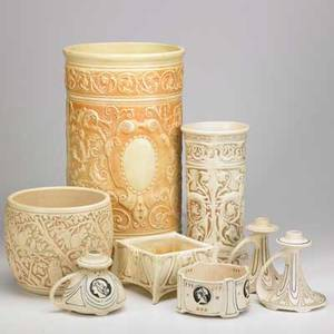Weller eight creamware pieces ivory jardiniere cylindrical vase low planter and umbrella stand together with cameo chamberstick and low bowl and pair of coatofarms chambersticks all unmarked u