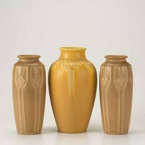 Rookwood three production vases pair in brown glaze with geometric design 1922 and one in golden yellow glaze with floral motif 1919 all marked tallest 10
