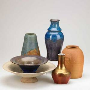 Art pottery six pieces two low bowls with floral rims in cream and violet flambe glaze three vases in purple glaze redware jar in oxblood gold and blue glazes decorated with carved faces some ma