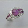 Art deco ruby and diamond platinum ring ca 1930 constructed in asymmetrical art moderne style an oval ruby cabochon 10mm x 8mm arrow shaped channel and rows of calibre cut rubies oec diamond