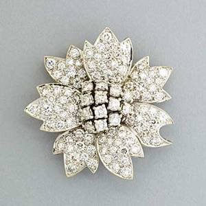 Diamond poinsettia blossom brooch 20th century pave diamond petals radiate from prong set diamond center approx 6 cts tw in 18k wg double pin back with hook for pendant wear 96 dwt 15 gs