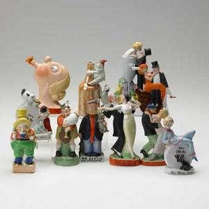 German porcelain figural bottles eleven include dancing figures comic characters scotsman etc 20th c tallest 5 14